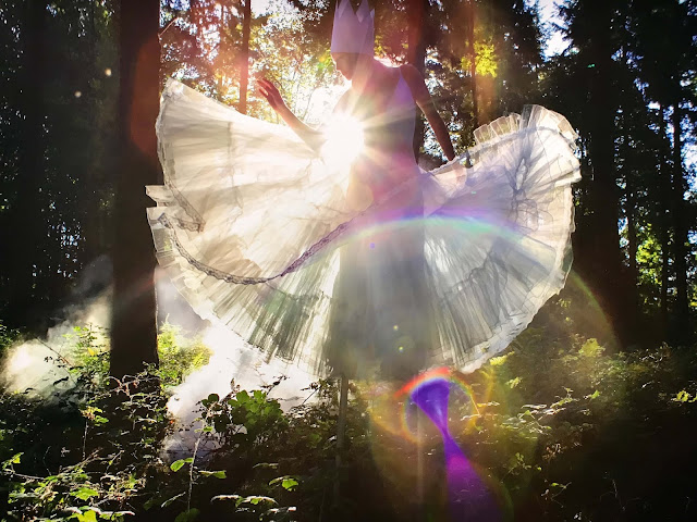 A blonde woman in a white dress on a sunny day, dancing through the meadows in a forest.