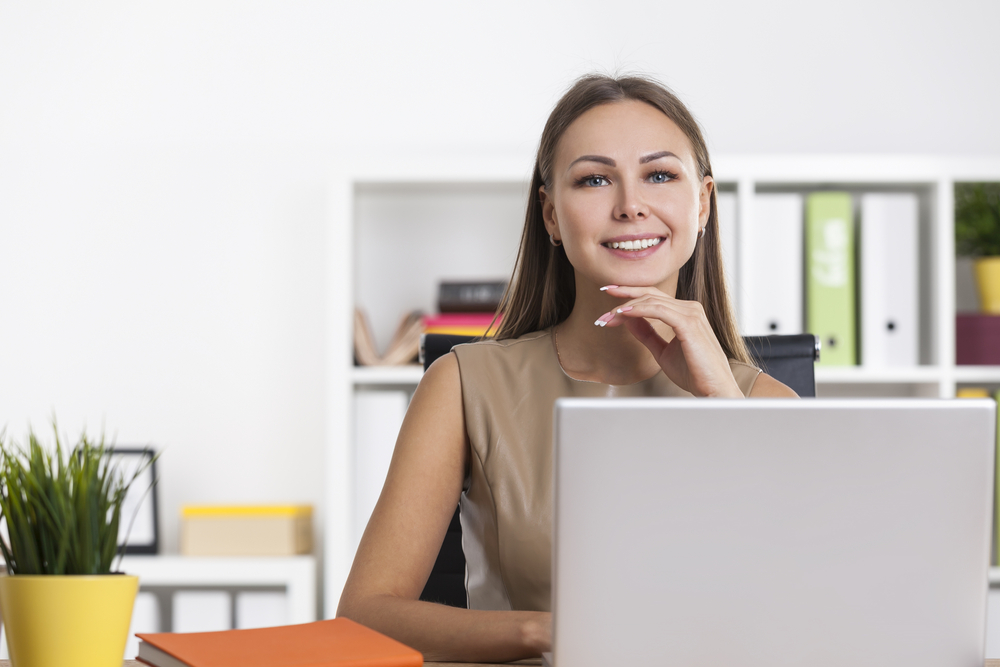 smiling woman sitting at her laptop computer