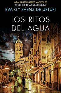 Portada del libro Los ritos del agua de Eva García Sáenz de Urruti con la editorial Planeta. Muestra una calle de Álava por la noche.