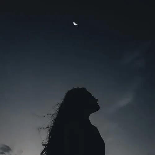 alone girl looking at half moon