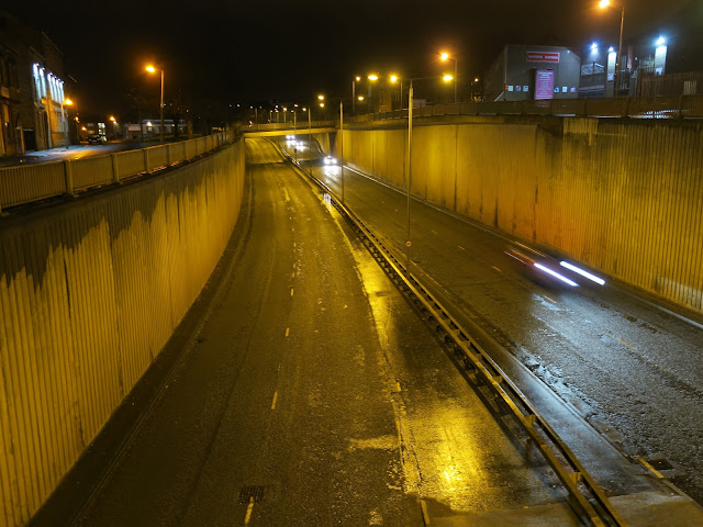 Cars at night dipping down under pedestrian bridges.