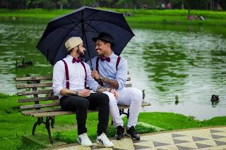 two gay boys sitting in a chair under an umbrella