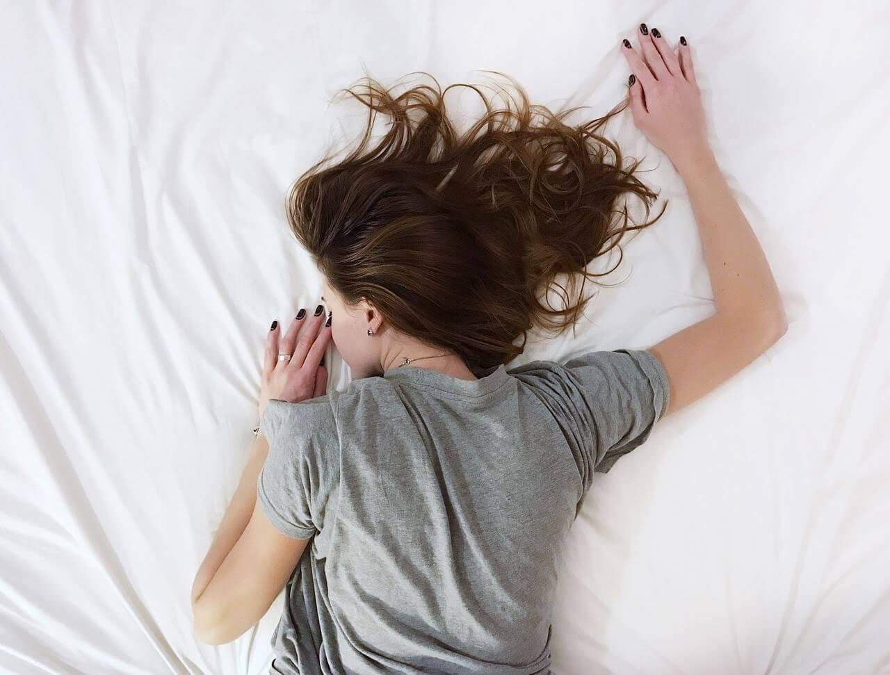 女の人が睡眠を得るためにベッドに横たわっている
