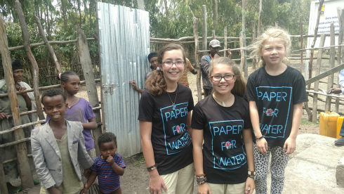 Three sisters who work for Paper for Water pictured with young girls who benefit from the charitable organization