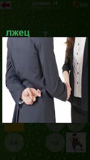мужчина лжец здоровается и держит пальцы перекрещивая их