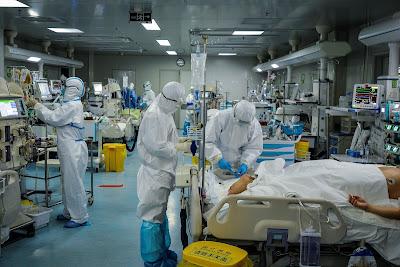 Foto tirada em 24 de fevereiro de 2020 mostra a equipe médica tratando de pacientes infectados pelo coronavírus COVID-19 em um hospital de Wuhan, na China (Photo by STR/AFP via Getty Images)