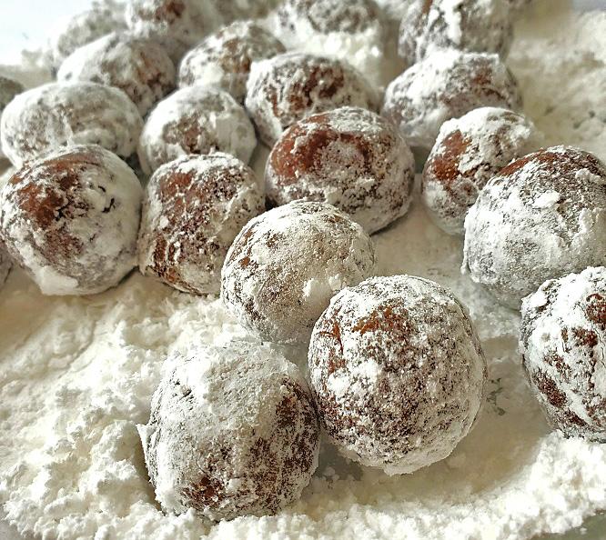 rum balls in a pie plate rolling in powdered sugar