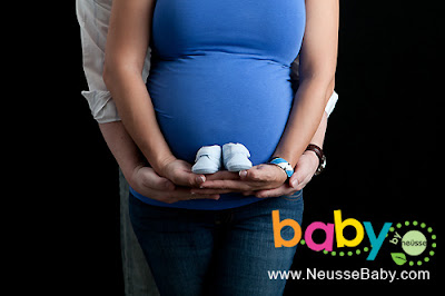 Maternity portrait in blue shirt holding belly bump and newborn shoe