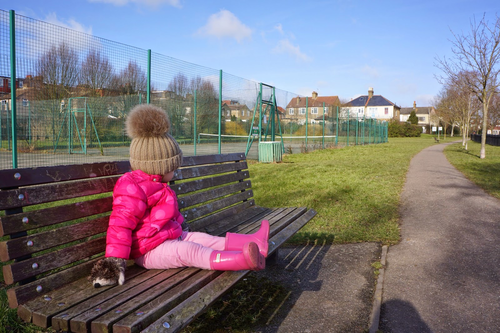 little girl sitting on a park bench