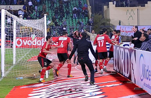Al-Ahly players escape from the field as fans of Al-Masry rush after them