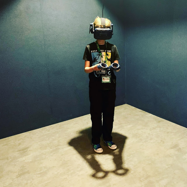 madmumof7's youngest son wearing headset and holding controllers at DNA VR