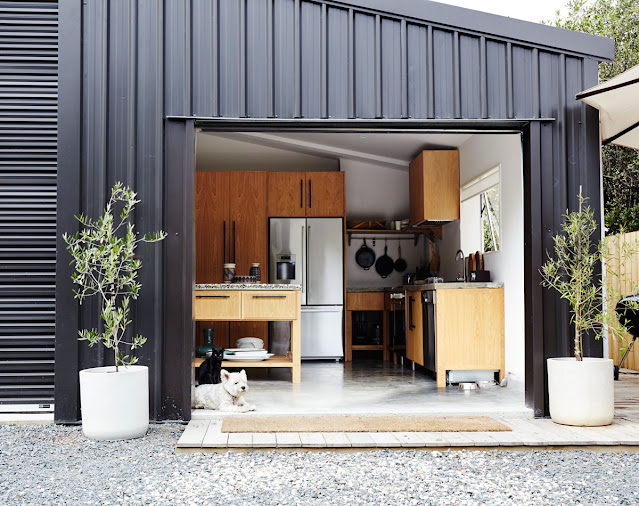 black metal corrugated exterior with large door open to the patio, oversized white planters with olive trees