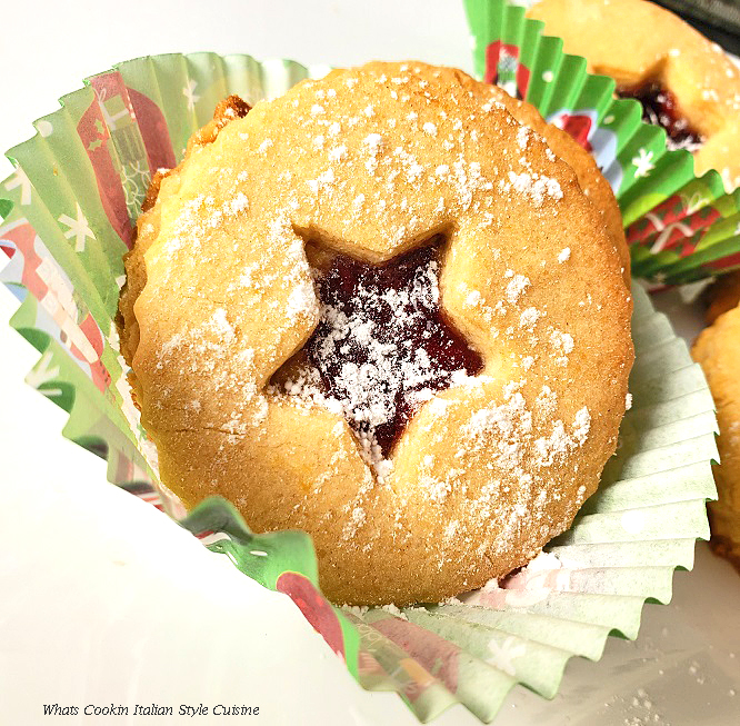 this is a linzer cookie filled with raspberry jam in a christmas paper liner with Santa on it