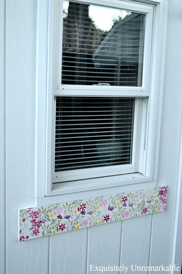 Painted Floral Board nailed to white pool cabana under window
