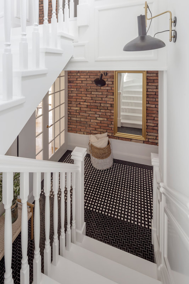 Escalera con barrotes de madera blanca y paredes con zócalos y molduras