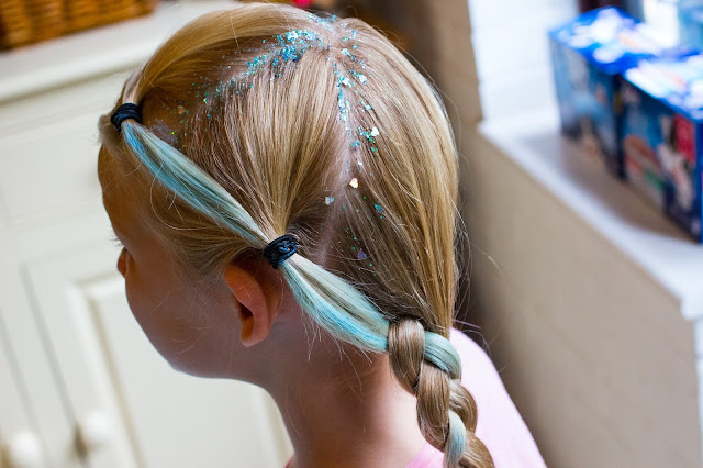 A hair plait with a blue streak and glitter on the parting