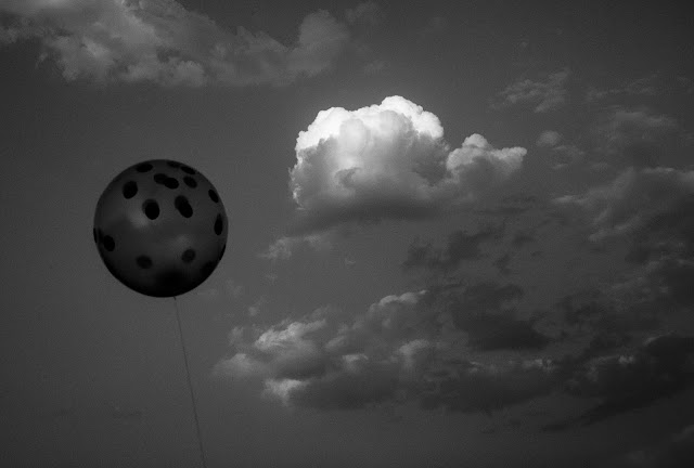 A Black and White Minimal Art Photograph of Balloon Versus Cloud.