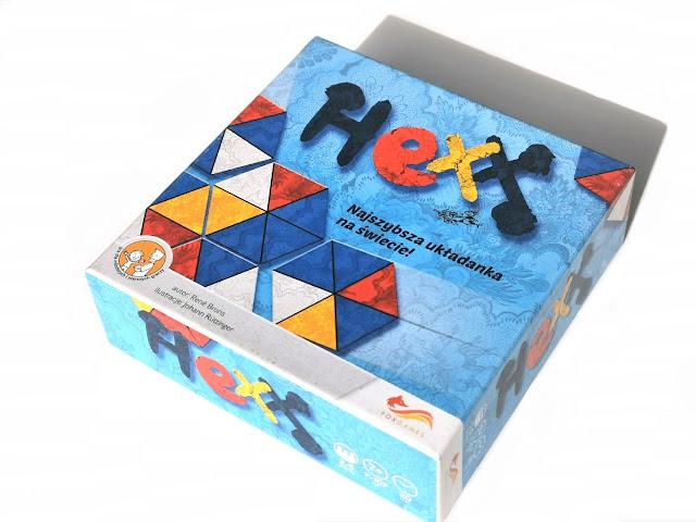 na zdjęciu pudełko gry Hexx, kwadratowe w kolorze niebieskim z napisem Hexx i ilustracjami kart z gry