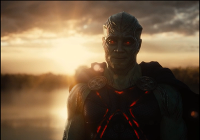 J'onn J'onzz standing outside of Bruce Wayne's house with a lake behind him in early morning, head slightly cocked to one side and smiling.