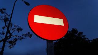 Señal de dirección prohibida al atardecer