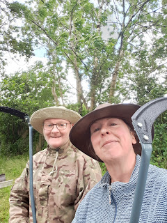 Two middle aged people in hats, holding scythes, standing in a field. They are grinning like proverbial idiots.