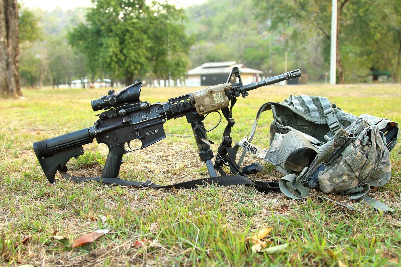 military rifle propped up on backpack with trees in the background for blog post about tv show combat missions