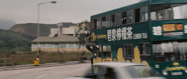 Jackie Chan hangs onto the side of a bus for dear life.