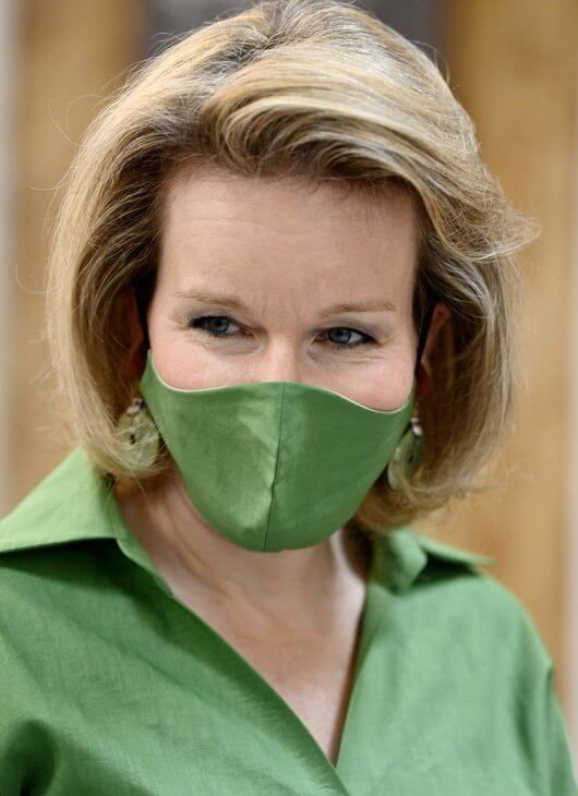Queen Mathilde wore a green belted shirt dress from Natan, and she carries Fabienne Delvigne cluth bag