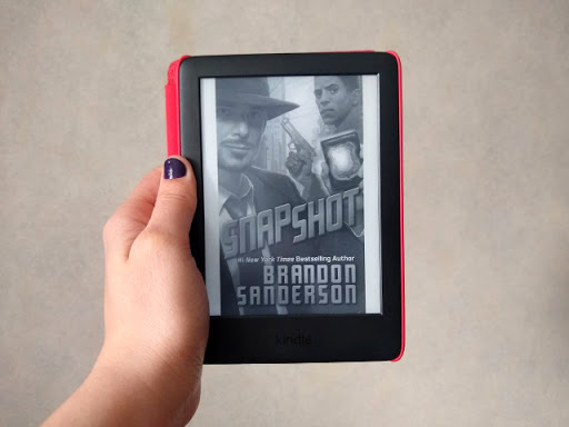 A hand holding a kindle with the Snapshot book cover.