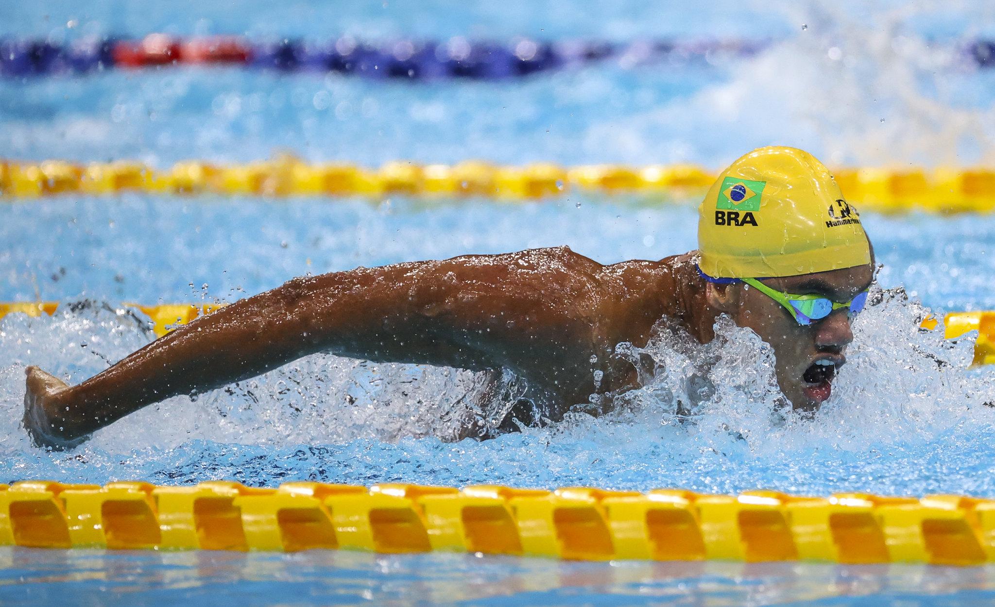 Wendell Belarmino fazendo o nado borboleta. Ele usa óculos verde e touca amarela e está com os braços para trás.