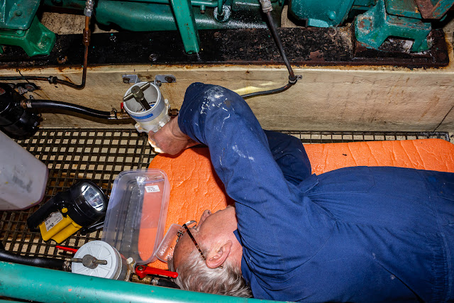 Photo of Phil removing the bowl from the pre-filter on Ravensdale's starboard engine