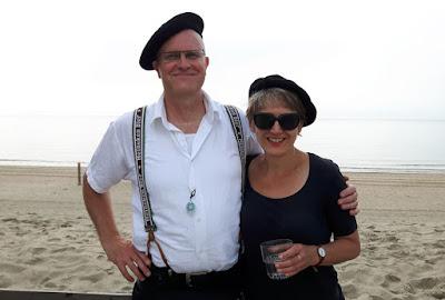 karikaturist Hugo en karikaturist Marion met alpinopet op het strand aan zee