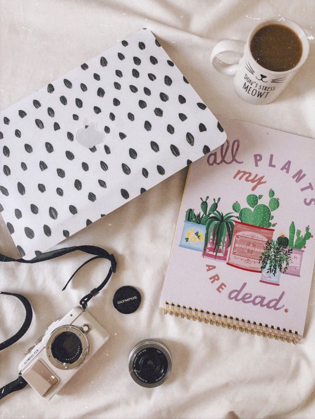A flatlay against a white bedsheet featuring a MacBook with a brush stroke sticker, a mug of coffee, dismantled camera and calendar reading 'all my planets are dead'