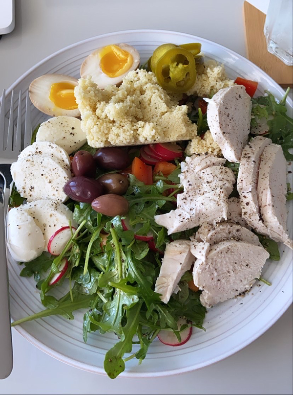 A salad composed of a ramen egg, pickled jalapenos, olives, couscous, bocconcini cheese, poached chicken, radishes, red peppers, and arugula