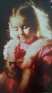 The author as a young child, with blonde hair and dressed in a pink jacket with a pink faux fur collar. She is looking down at a red rose.