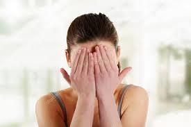 Mulher escondendo o rosto com as mãos