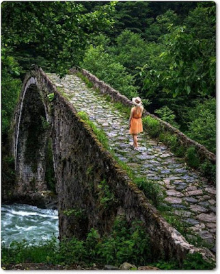 Uma jovem caminhando numa ponte de pedra em paisagem arborizada. #PraCegoVer