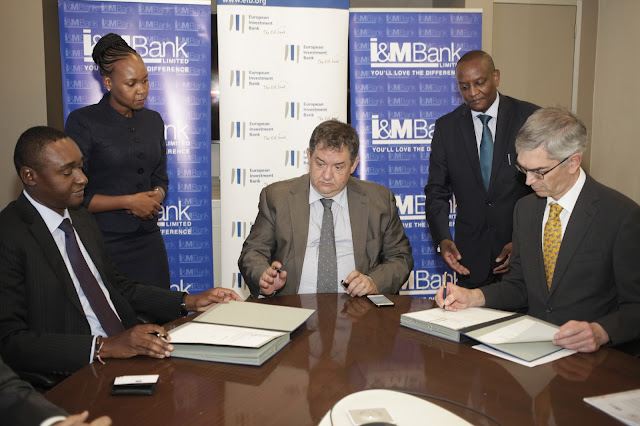 I&M Bank Kenya Chief Executive Officer Kihara Maina (left) and European Investment Bank executive responsible for EIB business financing outside Europe Robert Schofield (right) sign new line of credit for onward lending to the bank's SME, Corporate and Institutional Customers. The signing was witnessed by EU Ambassador to Kenya Stefano Dejak (centre), I&M Bank Kenya Legal Manager Peris Chege (standing left) and I&M Bank Kenya General Manager, Treasury, Henry Kirimania.