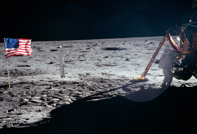 Wide shot of American flag at extreme left, total black on the horizon, Neil Armstrong with back turned at extreme right