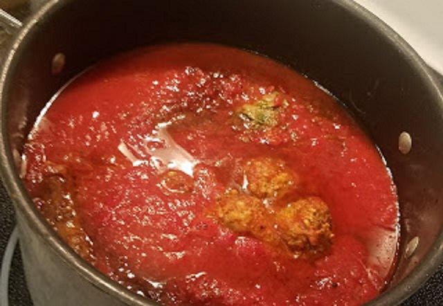 this is a pan of Italian homemade tomato sauce with meatballs and sausage simmering