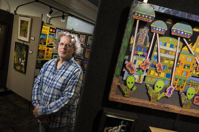 El artista Jerry Steffen Jr. está de pie al lado de una de sus obras. Jerry lleva camisa a cuadros, tiene pelo canoso y gafas. La obra es una representación de lo que parece ser una invasión a una ciudad con naves espaciales y extraterrestres