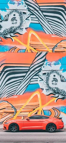 خلفية سيارة موستنج برتقالية اللون أمام لوحة جدارية