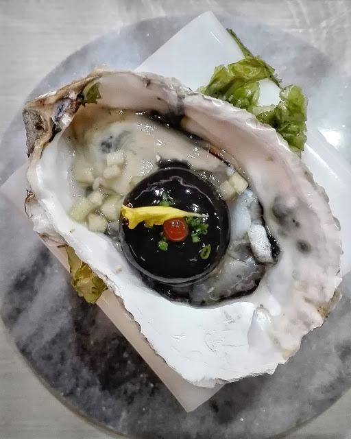 Ostra con esfera de aperitivo andaluz, tinta de calamar, fino y manzanilla
