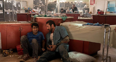 Movie still for Stuber where Kumail Nanjiani and Dave Bautista sit behind a red cabinet in a veterinary office and wait for the shooting to stop