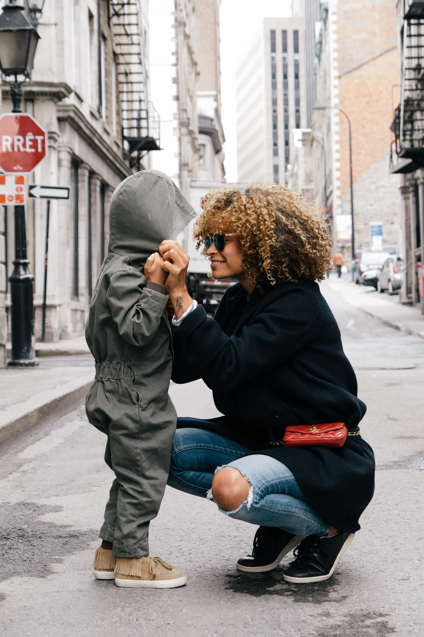 woman and toddler are wearing stylish outfits and posing on the street