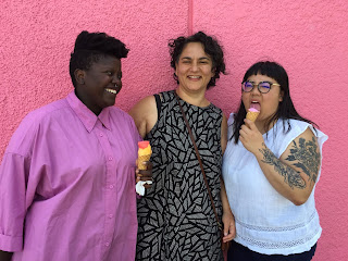 Three women eating ice cream in front of a pink wall - the director and 2 of the participants, Lydia and Joanne.