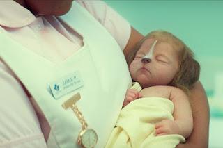 Baby human/animal hybrid held by a nurse