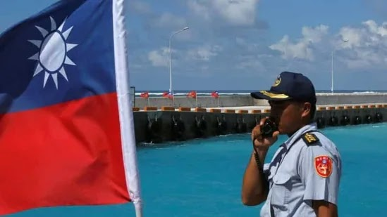 A member of the Taiwanese Coast Guard stands guard next to a Taiwanese flag on Itu Aba