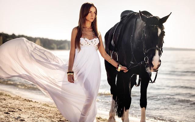 Een vrouw met haar paard op het strand