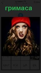 девушка в красной шапке сделала гримасу на своем лице